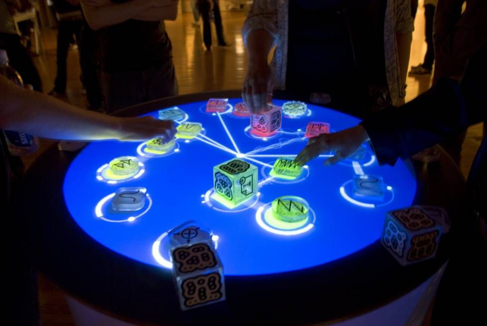 "An example of tangible interaction design for ""doing"" - the ""Reactable"". Note informational cues that inform the user of what each block does are visual, the tactil"