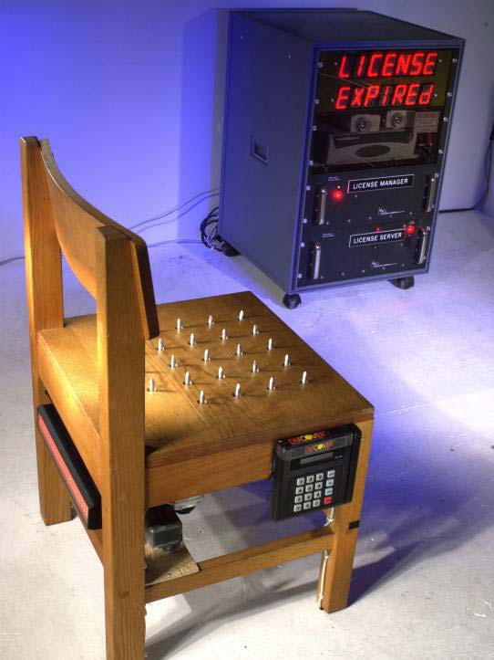 Wearable computing exhibit at San Francisco Art Institute 2001 Feb. 7th. This exhibit comprised a chair with spikes that retract for a certain time period when a credit card is inserted to purchase a